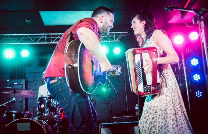 Fortunate Ones Performing On Stage With Guitar And Accordion