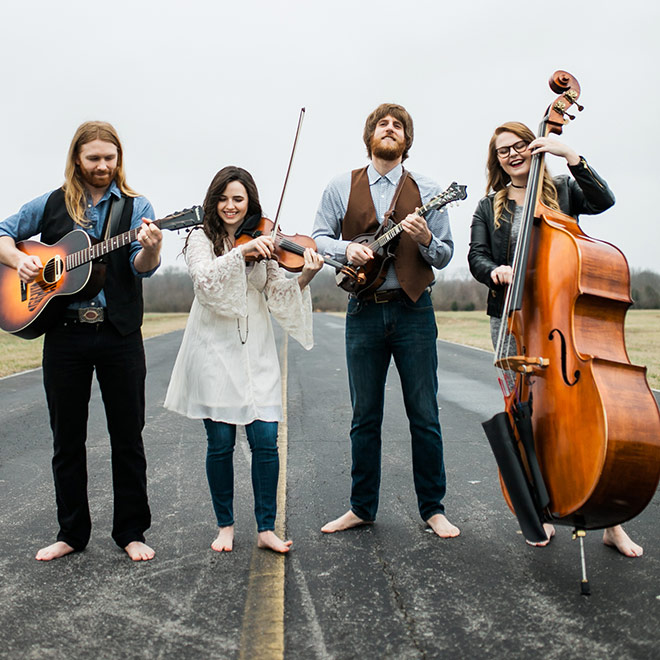 Barefoot Movement promo shot of band holding their instruments standing on a road