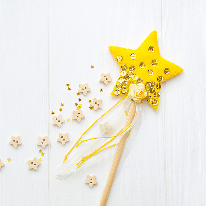 Yellow star wand with wooden flowers scattered around it