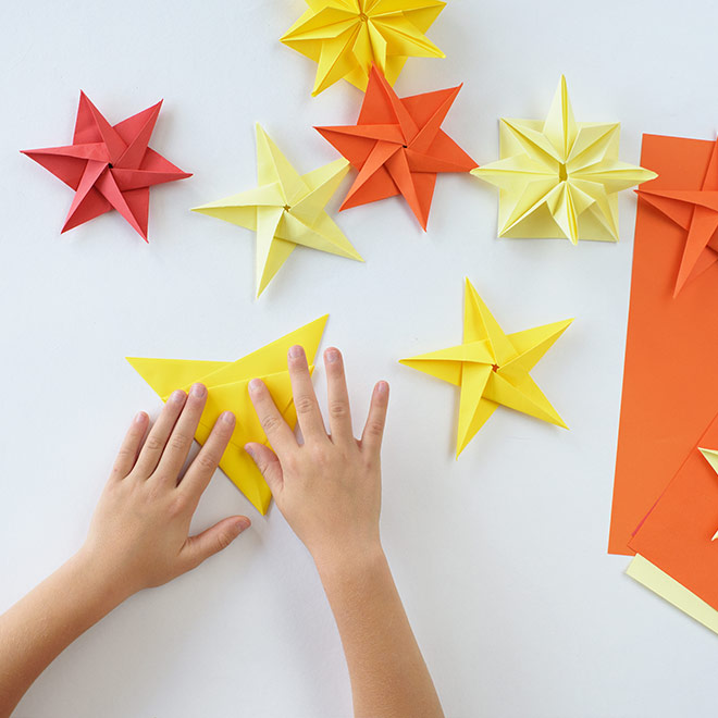 Child making origami stars