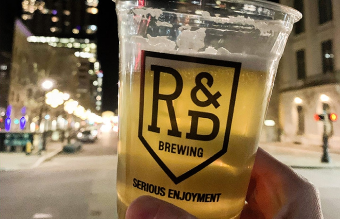 Person Holding A Beer With R&D Brewing Logo On It With Raleigh Skyline In Background