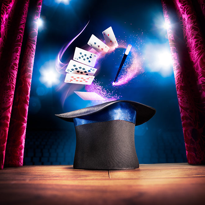 Top hat with cards and want hovering above on a stage