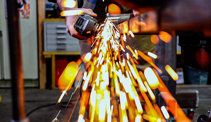 Artisan Grinding Metal With Sparks Flying
