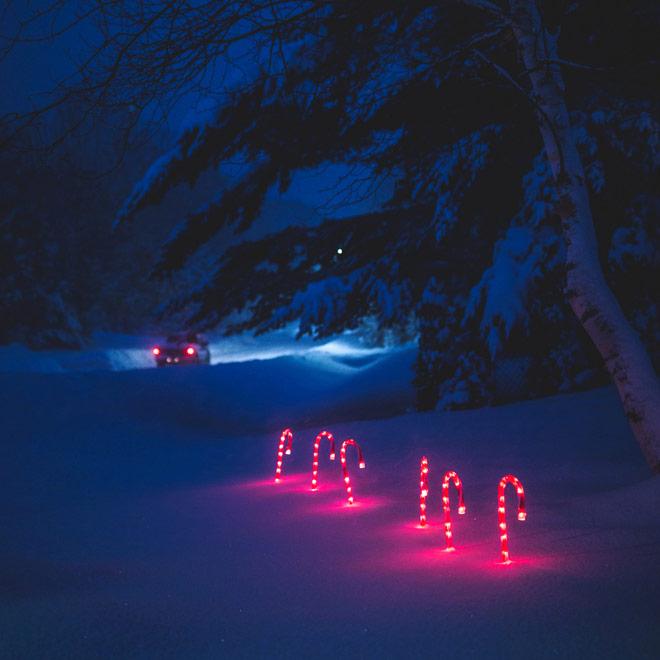 Lighted candy canes in snow at dusk